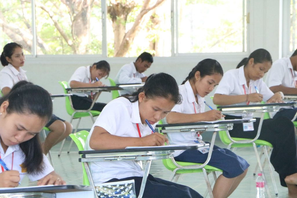 students in Cambodia writing exams